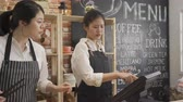 two asian women wearing apron working as barista in cafe shop counter. Filmati Stock