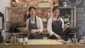 two happy female staff working in counter cafe store.