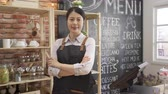 confident female barista standing behind counter in coffee shop. Stock Footage