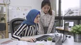strict malay female boss scolding young member of chinese woman staff or subordinate sitting in front of computer screen. Stock Footage