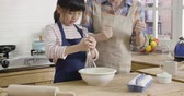 slow motion chinese little girl and beautiful mother apron smiling while baking at home. Stock Footage