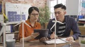 two asian woman and man colleagues sitting at wooden table in green office discussing about windmill models. female architect check project showing digital tablet screen to male manager partner team Filmati Stock