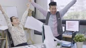 young asian female and male colleagues excited by celebrating victory looking at computer screen and high five together. Vidéos Libres De Droits