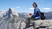 Adventure asian woman with bottled water sitting on rock in mountain peak in yosemite. Stock Footage