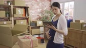 Young pregnant woman entrepreneur checking products stock on tablet at home office.