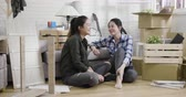 Young family asian sisters relax while assembling furniture at new house. Vidéos Libres De Droits