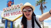 Young asian woman tourist finish video call standing outdoor by welcome to fabulous las vegas sign. girl travel backpacker say good bye and kisses to camera. female visitor in summer america trip.