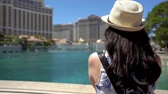 back view young asian woman tourist leaning on railing and looking at fountain in famous hotel in las vegas under sunlight flare. girl traveler having luxury trip to america in summer break. Stok Video