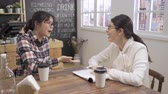 Two asian women laughing during job interview cafe bar.