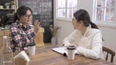 young Asian professional woman in interview meeting. woman interviewer laughing out loud naturally while listen fresh graduate girl candidate introducing herself in cafe bar