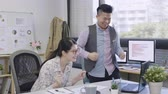 slow motion small business team high five in creative office.  happy asian man and woman coworkers with computer celebrating victory.