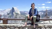 beautiful female hiker in cap relaxing in yosemite sightseeing looking around. Stok Video