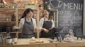 roddelen : two asian women in aprons laughing and standing behind counter while working in cozy small bakery together.