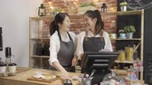 serveuse : Two young asian girl working together in counter of small cafe bar. Vidéos Libres De Droits
