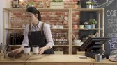 fast forward coffee shop owner woman keeping everything clean. Pretty lady barista stand behind cafe counter using rag wipe wooden table.