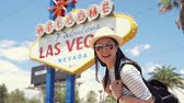 happy tourist woman with backpack walking by Las Vegas sign. girl in sunglasses having fun in front of Welcome to Fabulous Las Vegas billboard at Nevada USA.