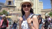 happy girl backpacker travel in summer las vegas. young woman tourist face camera smiling and standing under blue sky.