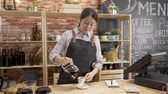 与える : smiling female barista serving drink to customer in cafe store. 動画素材