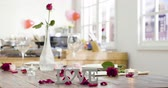 romantic valentines day indoors in cozy apartment kitchen in background. red roses, candles and flowers petals falling down around.