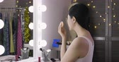 celebridade : Woman applying makeup near mirror with light bulbs in dressing room. Vídeos