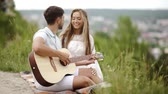afetuoso : Beautiful Couple In Love In Nature On Romantic Date, Spending Time Together. Handsome Young Man Playing Guitar While Beautiful Smiling Woman Enjoying Music. People On Picnic In Park