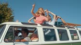 carro : Happy Friends Traveling By Car, Having Fun In Summer. Smiling Young Men And Beautiful Women Dancing And Laughing While Having Travel In Retro Bus With Open Car Roof.