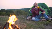 fogo : Man Traveling In Nature, Sitting Near Camp And Bonfire With Mobile Phone And Drinking Beer.