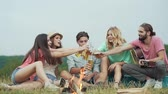 atividades de fim de semana : Happy Young Friends Drinking Beer, Having Fun And Sitting Near Bonfire On Picnic Outdoors.