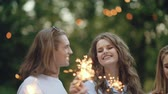 fogo : Happy Friends With Sparklers Having Fun Outdoors, Cheerful People Enjoying Party In Park.