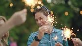 fajerwerki : Happy Friends With Sparklers Having Fun Outdoors, Cheerful People Enjoying Party In Park.