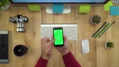 Flat Lay Of Man Hands Using Phone With Green Screen At Workplace