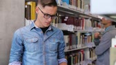 ders kitabı : Student At Library. Man Looking Books On Bookshelves Stok Video