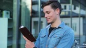 campus : Male Student Reading Notepad Outdoors At College