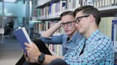 читатель : Students Reading Book At College Library Near Bookshelves Стоковые видеозаписи
