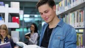 ders kitabı : Library. Smiling Male Student Reading Book Near Shelves
