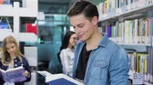 estante : Library. Smiling Male Student Reading Book Near Shelves