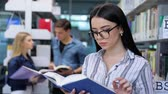 leitor : Library. Smiling Woman Reading Book Near Shelves In University Stock Footage