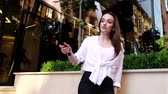 blogger : Video Blogging. Woman With Camera Near Modern Business Building Stock Footage