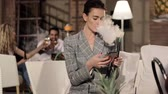 fumante : Woman Smoking Hookah And Using Phone At Shisha Lounge