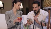 dym : Man And Woman Smoking Shisha, Drinking Cocktails And Using Phone