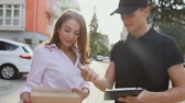 courier : Delivery Service. Woman Receiving Package From Courier, Signing Delivering Document Outdoors Stock Footage