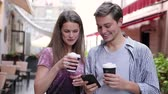 roupas casuais : Happy Couple Using Mobile Phone And Drinking Coffee Outdoors Vídeos