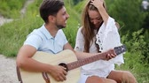 randka : Young Couple In Love On Date Outdoors. Romantic Man Playing Guitar And Singing For Woman In Nature Wideo