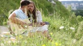 Young Couple In Love On Date Outdoors. Romantic Man Playing Guitar And Singing For Woman In Nature Stock Footage