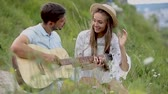 kapcsolat : Young Couple In Love On Date Outdoors. Romantic Man Playing Guitar And Singing For Woman In Nature Stock mozgókép