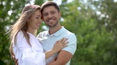 flört : Romantic Woman Kissing Man In Cheek In Nature. Happy Couple In Love Hugging Outdoors Stok Video