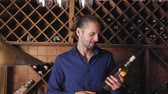 vitrin : Handsome Man Holding Bottle Of Wine In Cellar Winery