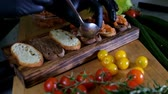 recipe : Man preparing Italian bruschetta with baked tomatoes, basil and cheese. Italian food slow motion