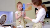 dziecko jedzenie : Young happy mother and her cute curly toddler daughterr in a kitchen to cook Wideo