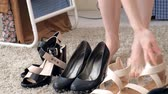 stylish : A woman tries on shoes, chooses from several pairs Stock Footage